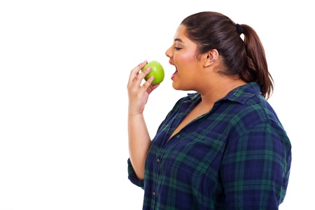 close up portrait of plus size young woman eating apple on white background photo