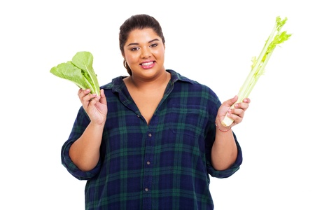 happy overweight woman holding green vegetables on white background photo