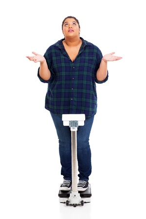 weighting: overweight young woman asking why when weighting herself