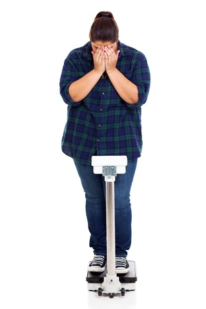 stressed out: unhappy overweight girl crying when weighting on scale Stock Photo