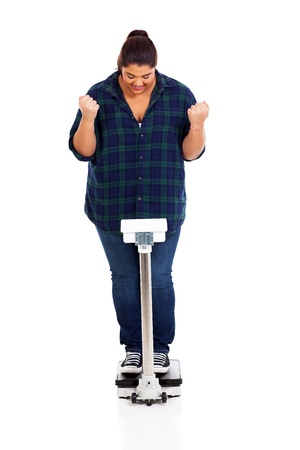 cheerful overweight girl on scale successful weight loss photo