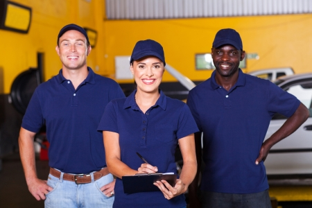 group of happy workers in auto repair shop photo