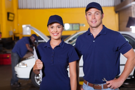 car in garage: two happy auto service center employees portrait inside workshop