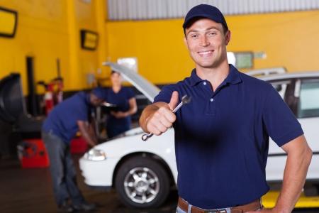 garage automobile: heureuse masculin mécanicien automobile renonçant au pouce tenant la clé