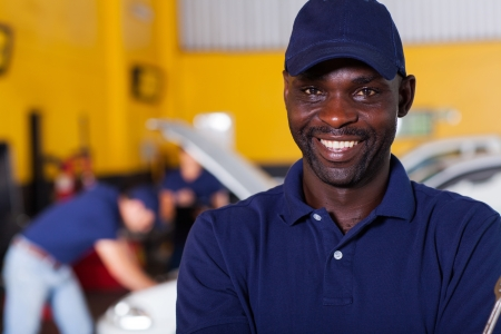 close up portrait of happy african male auto mechanic photo