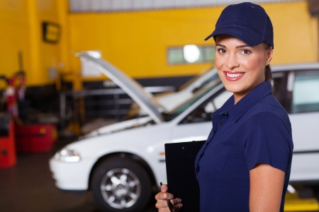 beautiful cheerful female auto garage manager portrait inside workshop photo