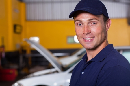 portrait of trustworthy auto mechanic inside workshop photo