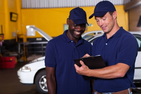 two happy auto mechanics going through checklist inside workshop photo