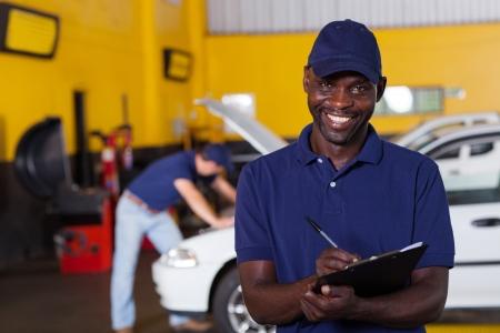 garage automobile: African American hommes rapport écrit de mécanicien de véhicule