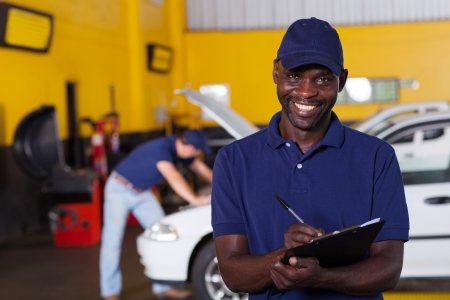 car workshop: male african american vehicle mechanic writing report