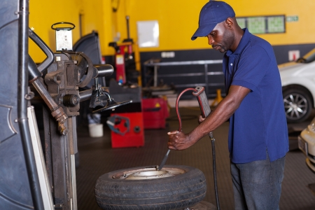 puncture: african auto mechanic pumping car tyre