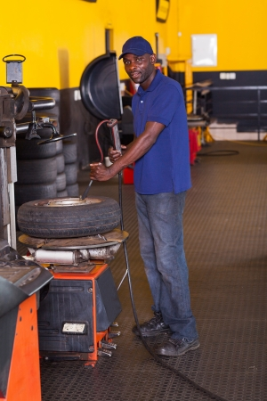 puncture: african tyre shop worker inflating a trye with professional machine