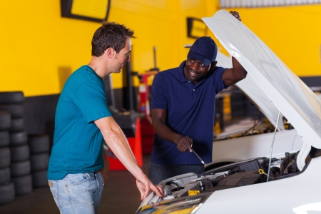 auto repair shop: african auto mechanic and customer discussing vehicle fault