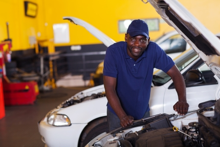 engine bonnet: male african car mechanic inside workshop