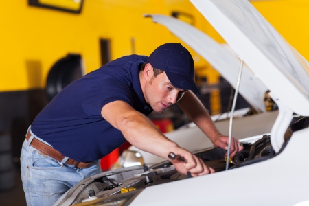 auto mechanic repairing vehicle inside workshop photo