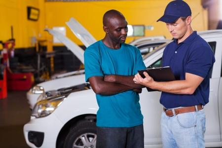 mechanical men: african man inside vehicle workshop with auto mechanic