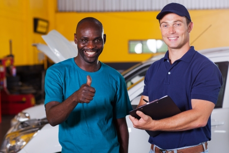 bonnet up: happy african customer giving thumb up in car repair shop