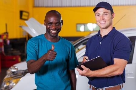mechanics: happy african customer giving thumb up in car repair shop