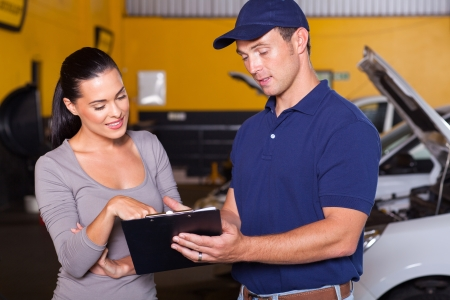 car workshop: auto mechanic and female customer in garage Stock Photo