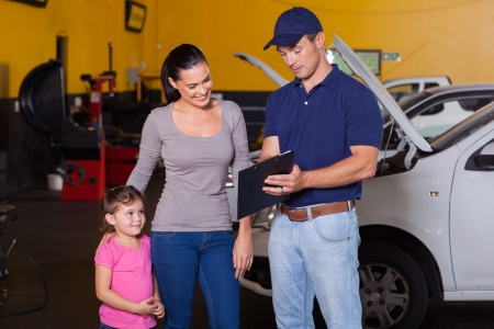 mother and daughter in garage with auto mechanic Stock Photo - 19202479