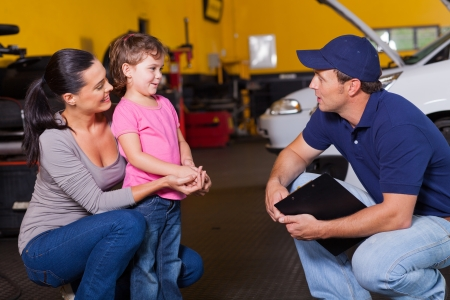 automobile workshop: friendly auto technician talking to customers little daughter in garage