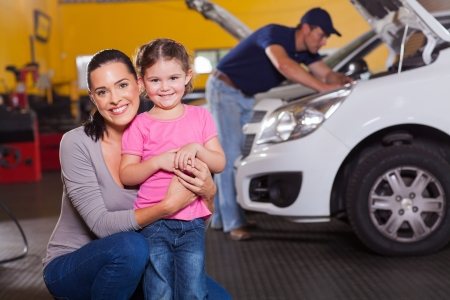 auto repair shop: happy young mother and little daughter in garage waiting their car to be serviced