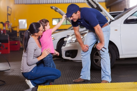 cute little girl playing with auto mechanic in garage photo
