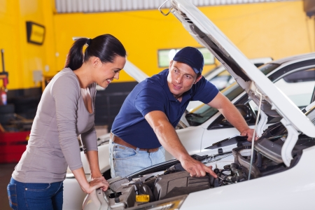 service car: friendly mechanic showing female customer her car problem in garage