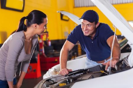 trustworthy: trustworthy auto technician talking to female customer in garage Stock Photo