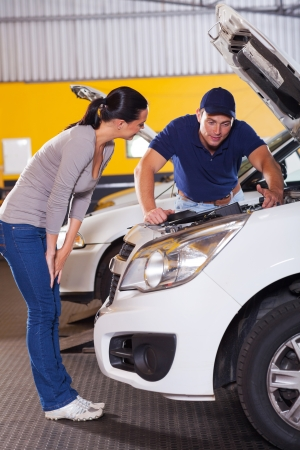 auto mechanic talking to female customer in front of her car with bonnet open photo