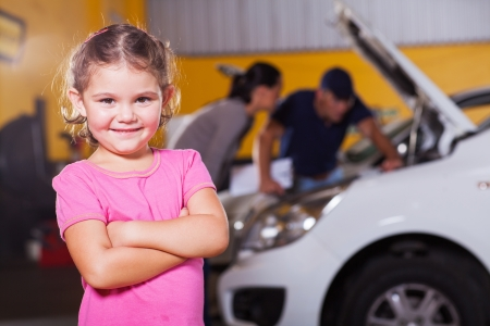 automobile workshop: cute little girl waiting for mother in garage