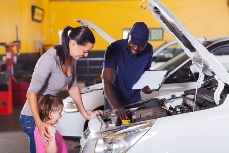 happy mother and little girl in car service center with auto technician photo
