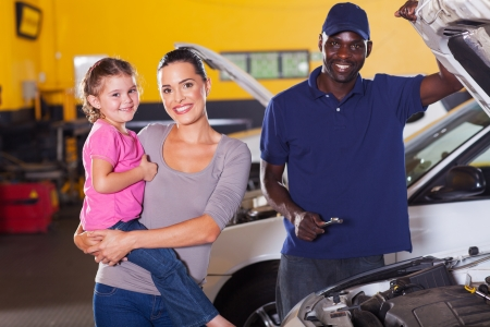 young mother and daughter in garage with auto mechanic photo