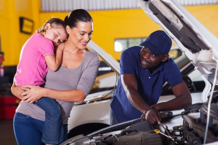 young mother taking her car for repair in garage with daughter sleeping on her shoulder photo