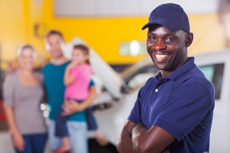 trustworthy african auto mechanic standing in front of family inside garage photo