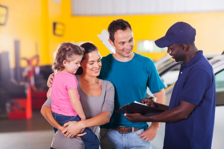 friendly auto mechanic talking to young family in garage photo