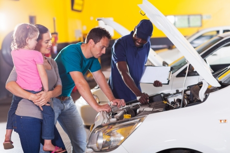 young family taking their car for repair in garage photo