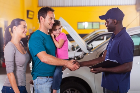 friendly auto mechanic handshaking with family inside workshop photo