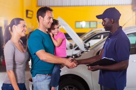 handshaking: friendly auto mechanic handshaking with family inside workshop