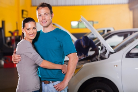 happy couple taking their car for service and waiting inside garage photo