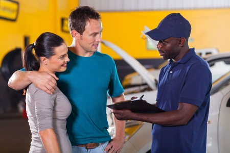 auto mechanic talking to young couple in repair shop photo
