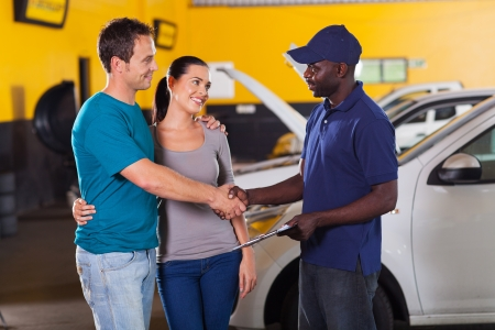 auto repair: african auto technician handshaking with young couple in garage Stock Photo