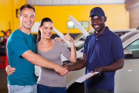 happy young couple giving thumb up to auto repair shop photo