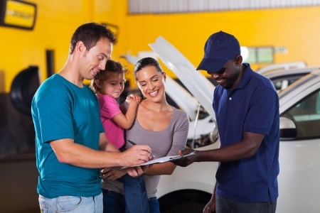 happy family man signing invoice in car repair shop photo