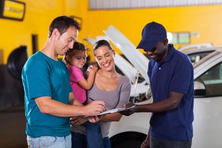 car repair shop: happy family man signing invoice in car repair shop