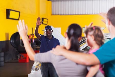 the farewell: amigable africano trabajador de la tienda de reparación de automóviles agitando adiós al cliente Foto de archivo