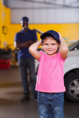 cute little girl wearing auto mechanics cap in repair shop photo