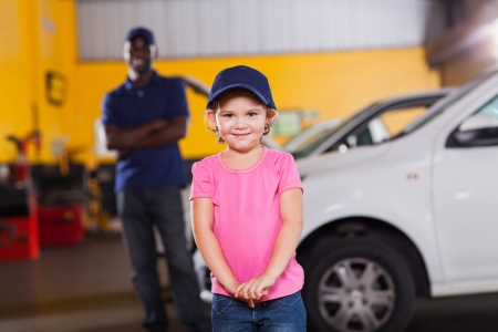 funny little girl wearing auto technician's cap in garage photo