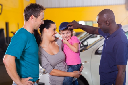 friendly african american auto mechanic playing with customers little girl photo