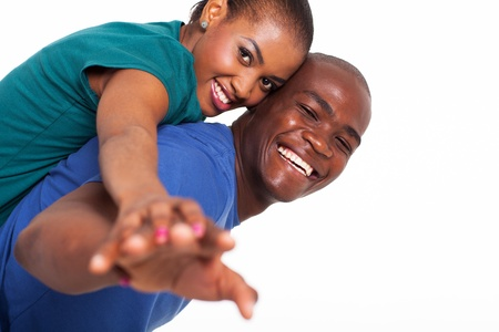 happy young african woman enjoying piggyback ride on boyfriends back with their hands outstretched photo